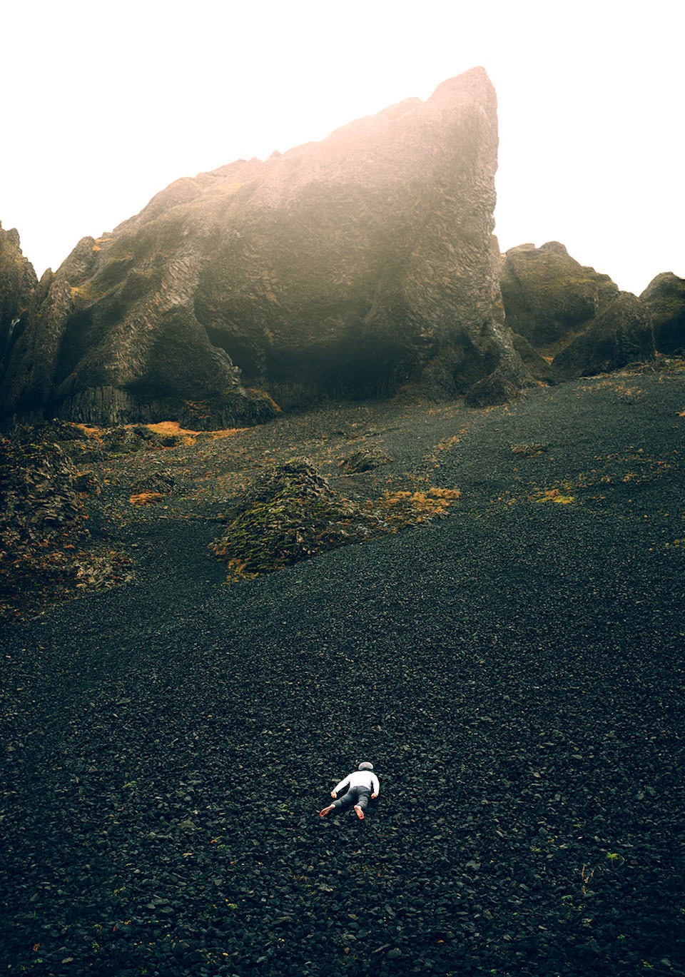 Ein Mensch liegt auf schwarzen Steinen vor einem Berg.