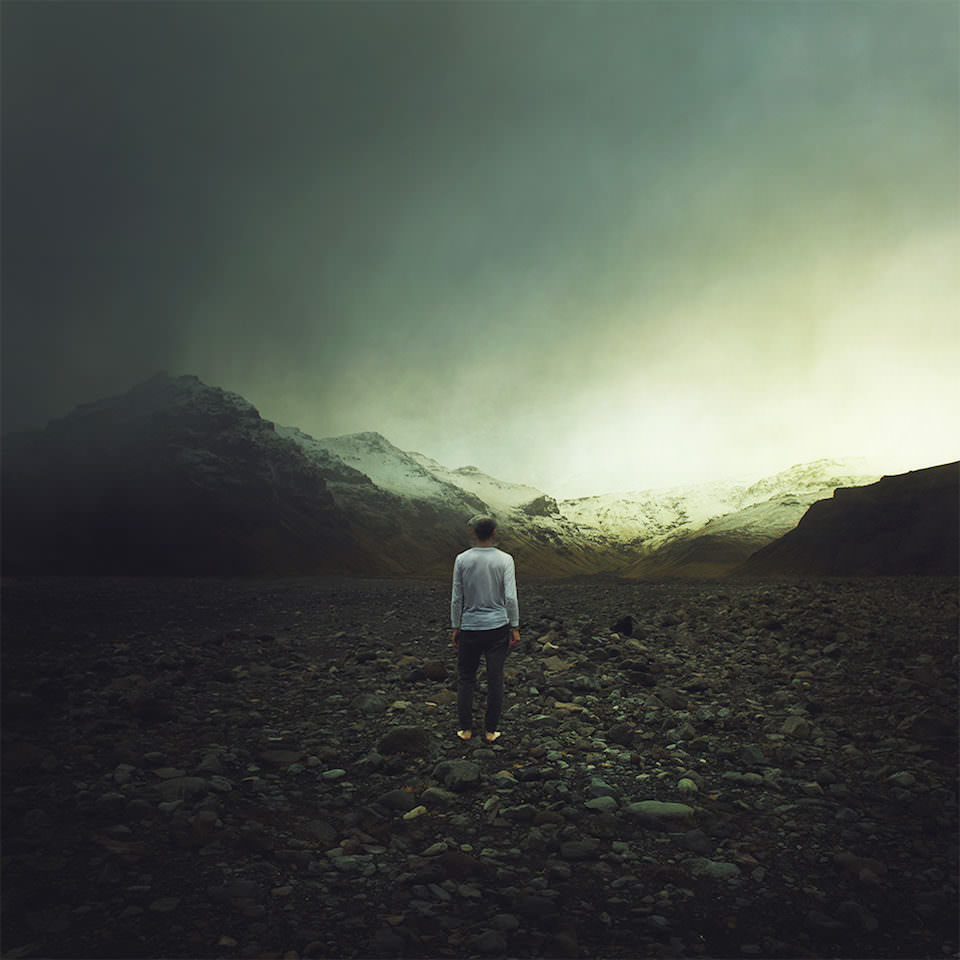 Person steht auf einem Feld mit schwarzen Steinen vor einer Bergkette