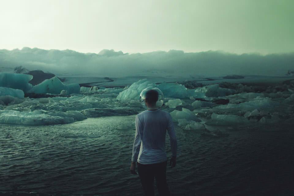 Ein Mann mit Fischglas auf dem Kopf steht vor einer Eislandschaft.