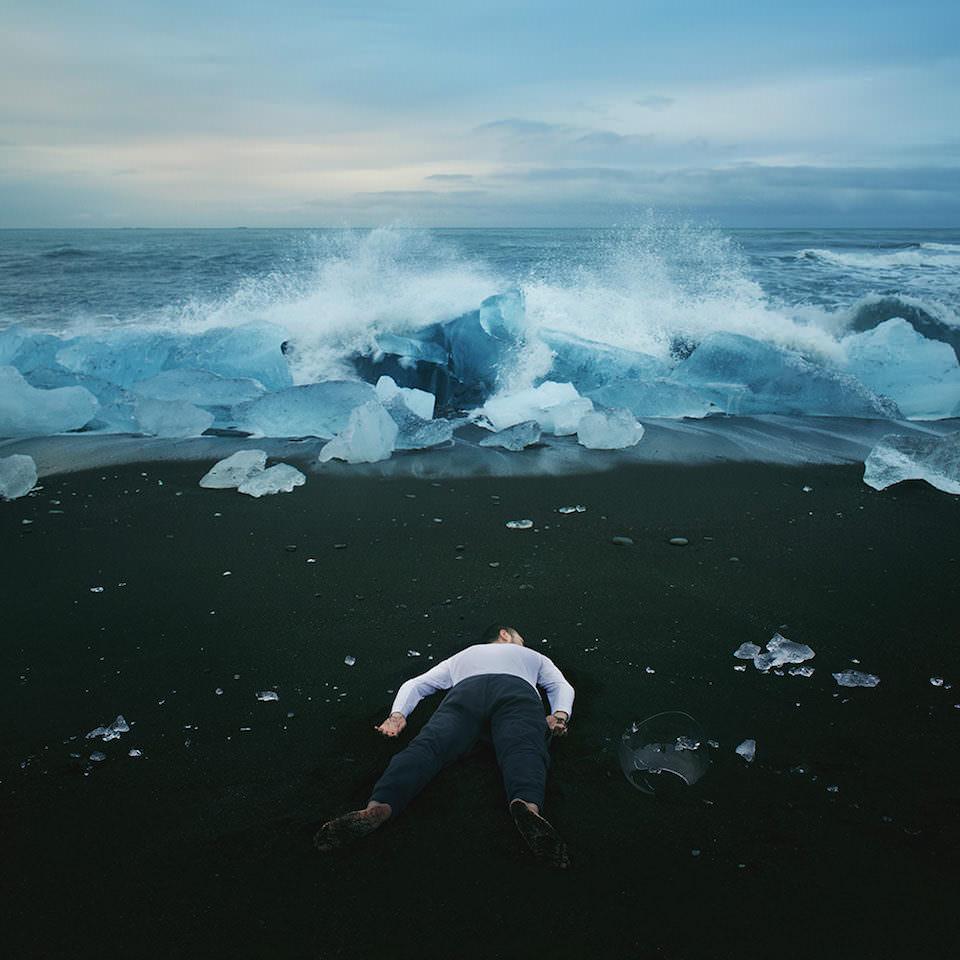 Ein Mann liegt an einem Strand mit schwarzem Sand. Die Brandung des Meer schlägt über das Eis vor ihm.