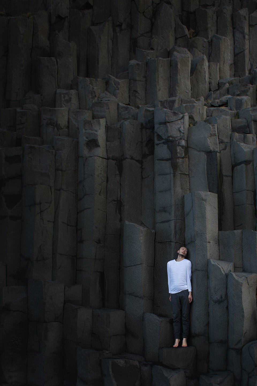 Ein Mann mit weißem Oberteil steht auf einer Felswand mit dunklem Stein.