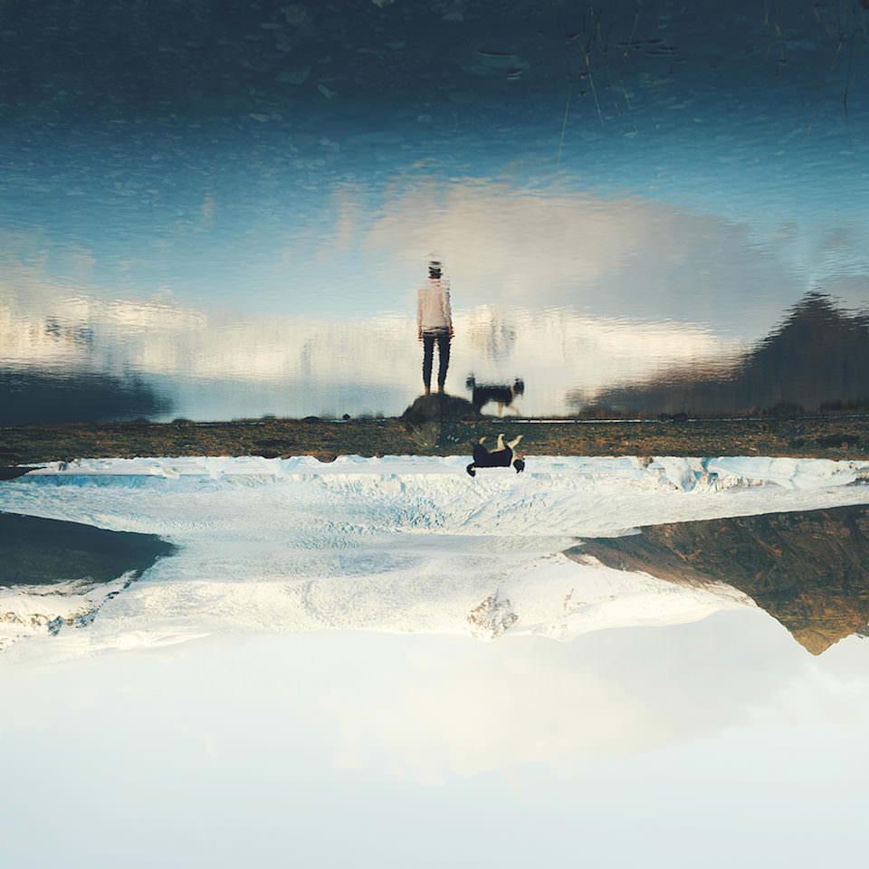 Die Reflektion eines Mannes, der vor einem See steht. das Bild steht auf dem Kopf und der Mann wurde aus dem Bild entfernt.