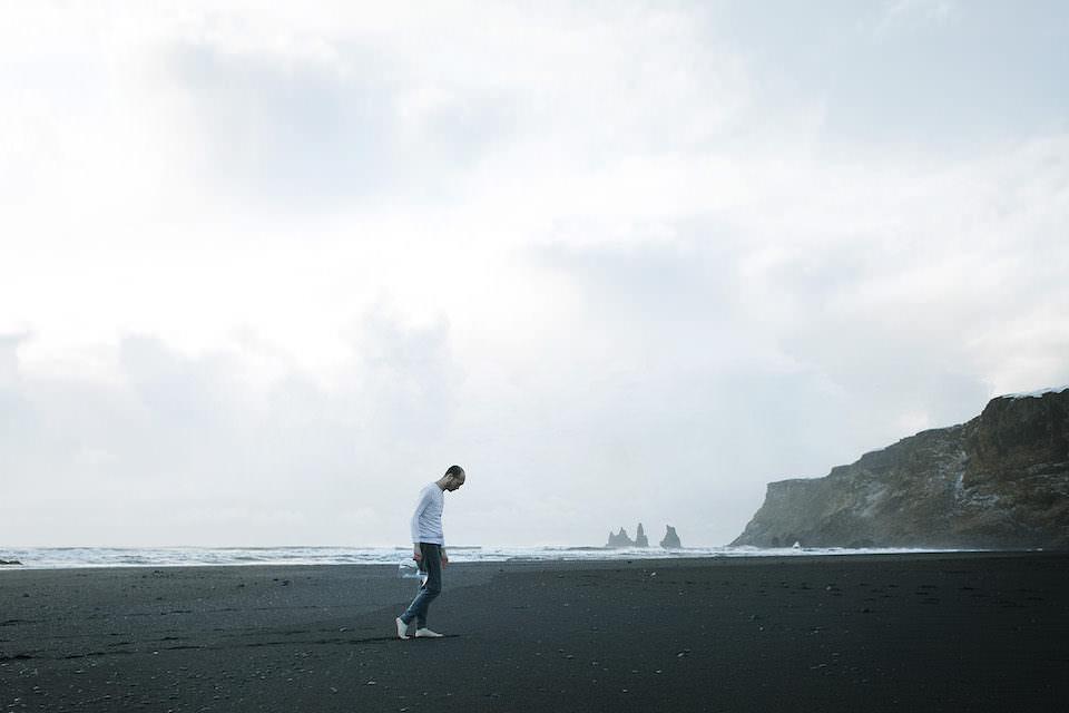 Ein Mann in weißem Oberteil geht über einen Strand mit schwarzem Sand.