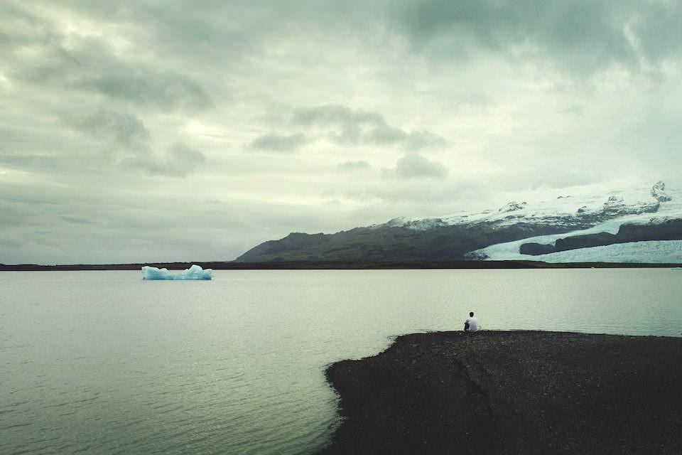 Ein Mann sitzt am Meer und blickt auf eine Berglandschaft. Im Wasser treibt etwas Eis.