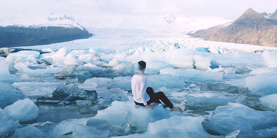 Ein Mann sitzt inmitten einer Eislandschaft und hat ein kaputtes Fischglas auf dem Kopf.