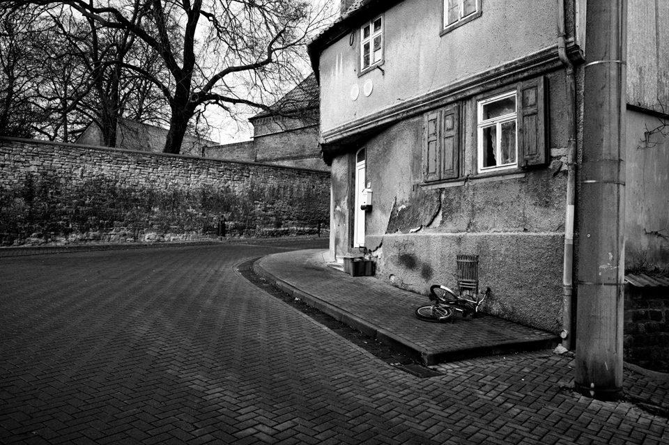Eine Straße führt um ein altes Haus