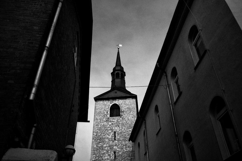 Ein Kirchturm zwischen zwei Häusern