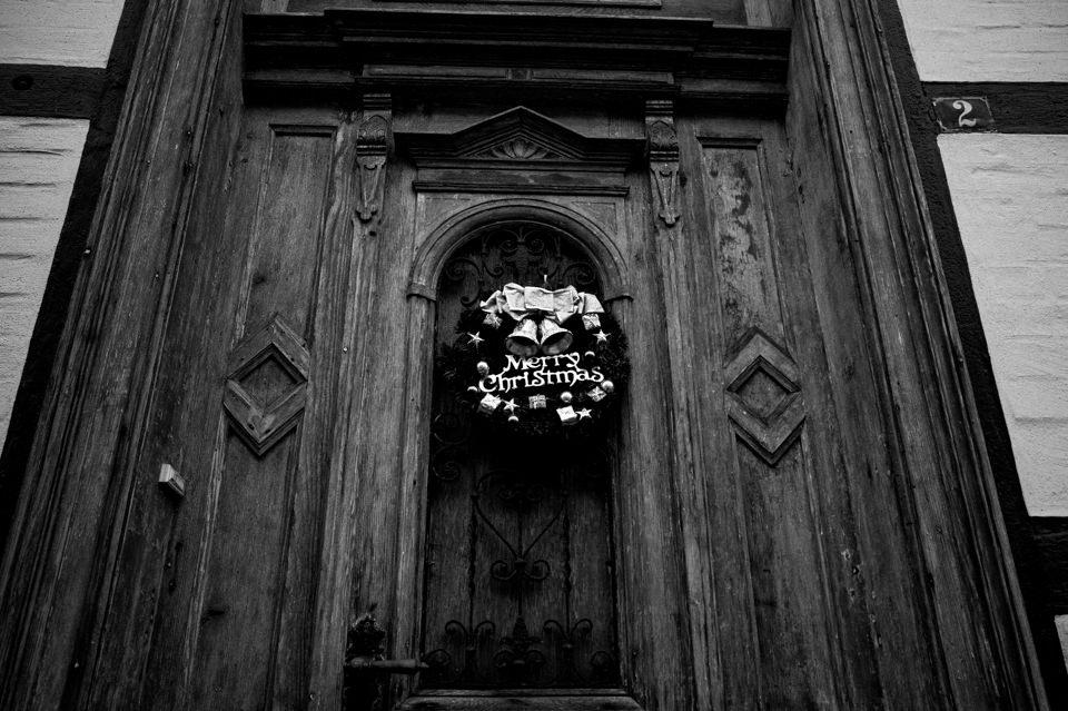 An einer Tür hängt ein Kranz