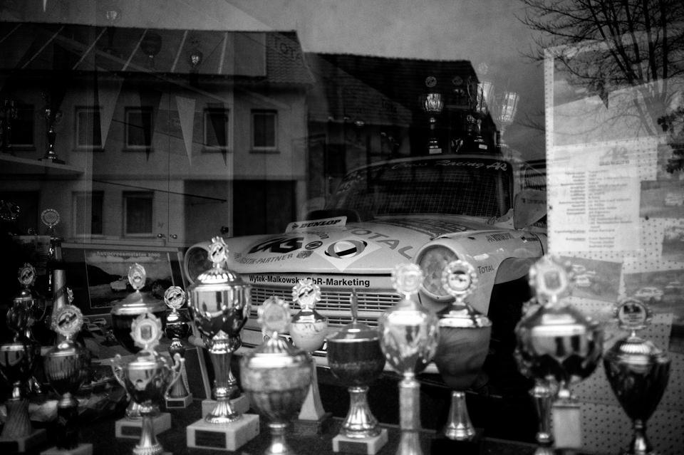 Hinter einer Scheibe stehen Pokale und ein Auto