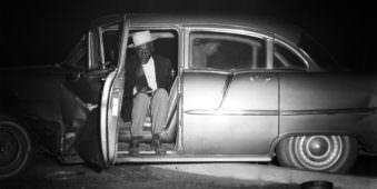 Eine Person sitzt der offenen Tür eines Autos
