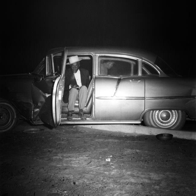 Eine Person sitzt in der offenen Tür eines Autos