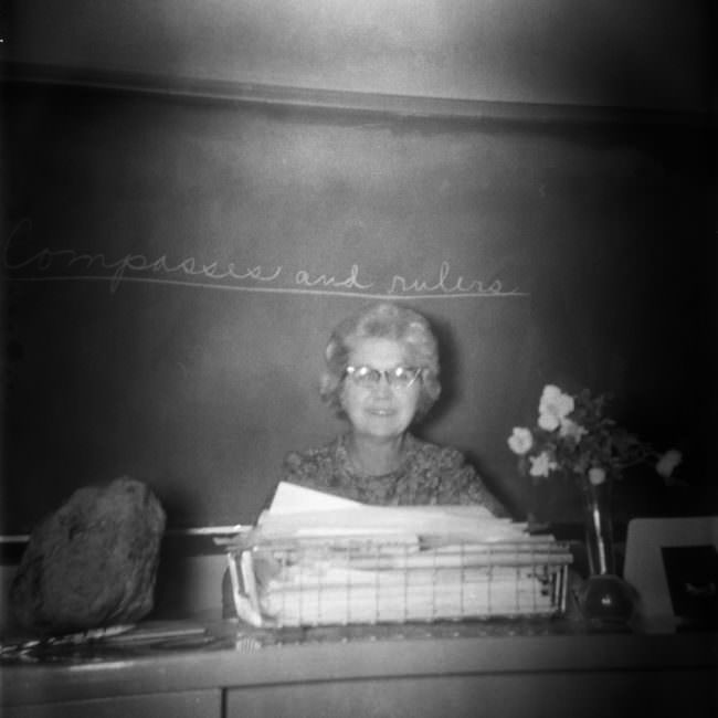 Eine Lehrerin sitzt an einem Pult