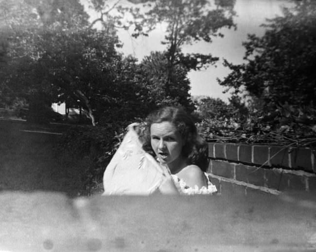 Eine junge Frau sitzt hinter einer Mauer