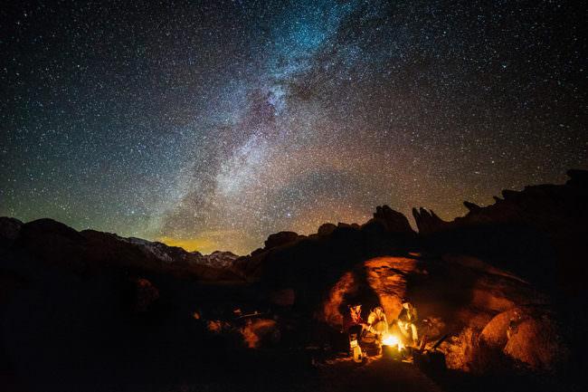 Menschen sitzen um ein Lagerfeuer unter Sternenhimmel