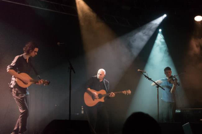 Ein Konzertfoto, auf dem drei Musiker zu sehen sind.