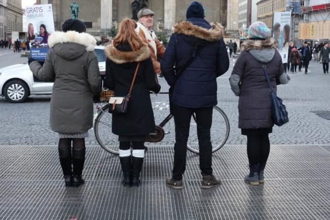Vier personen stehen mit dem Rücken zur Kamera.