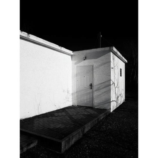 Surreal anmutende Hausecke bei Nacht.