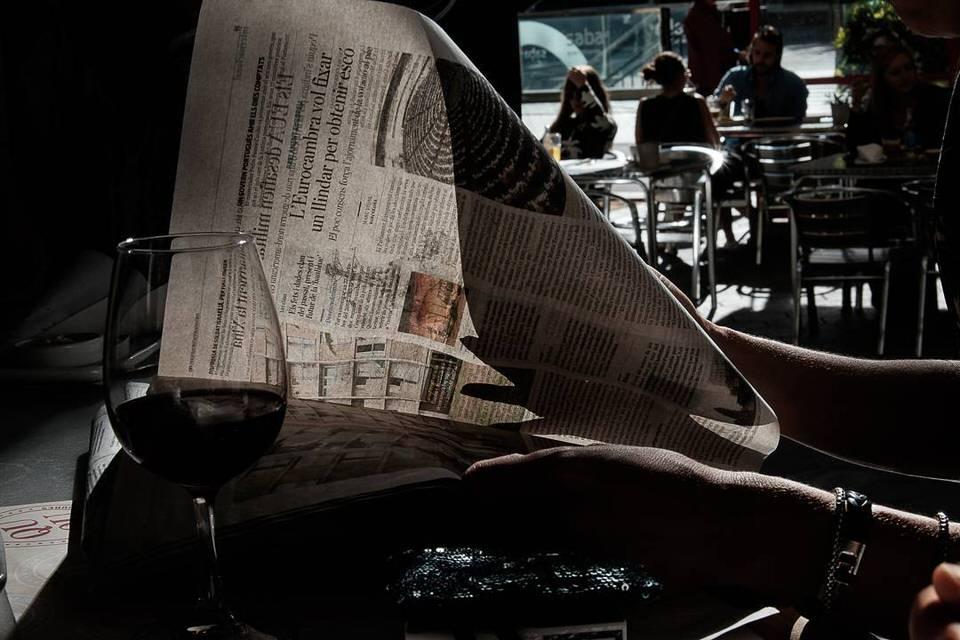 Man sieht ein Glas auf einem Tisch, dahinter eine aufgeschlagene Zeitung durch die man Hindurchblicken kann.