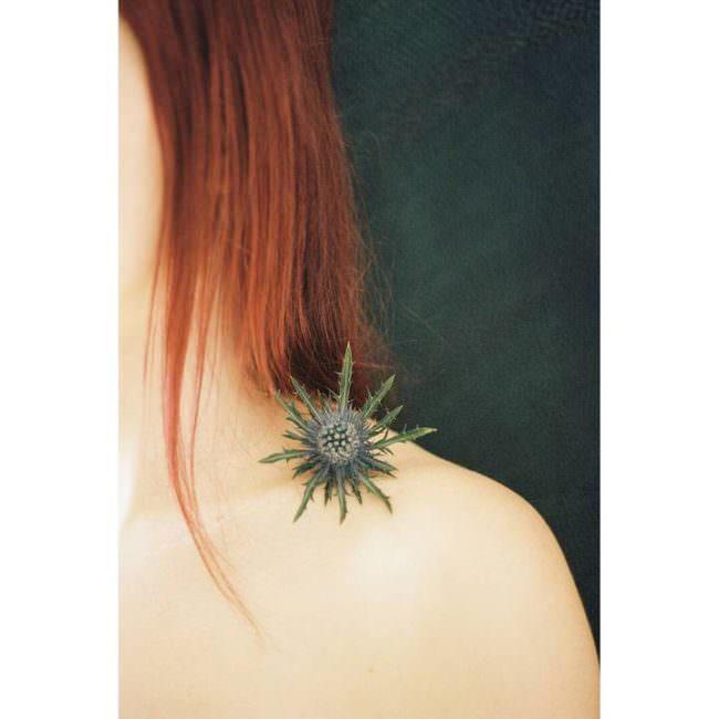 Nahaufnahme einer entblößten Frauenschulter auf der eine Blüte liegt. Sichtbar sind noch lange rote Haare.