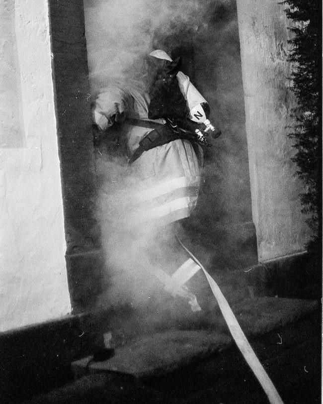 Ein Feuerwehrmann von hinten, der in ein scheinbar brennendes Haus rennt.