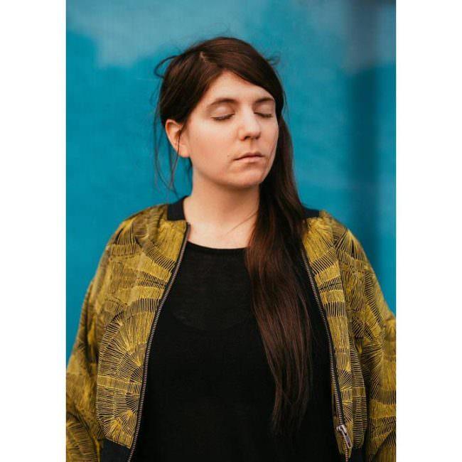 Portrait einer Frau mit gelber Jacke und langen dunklen Haaren mit geschlossenen Augen.