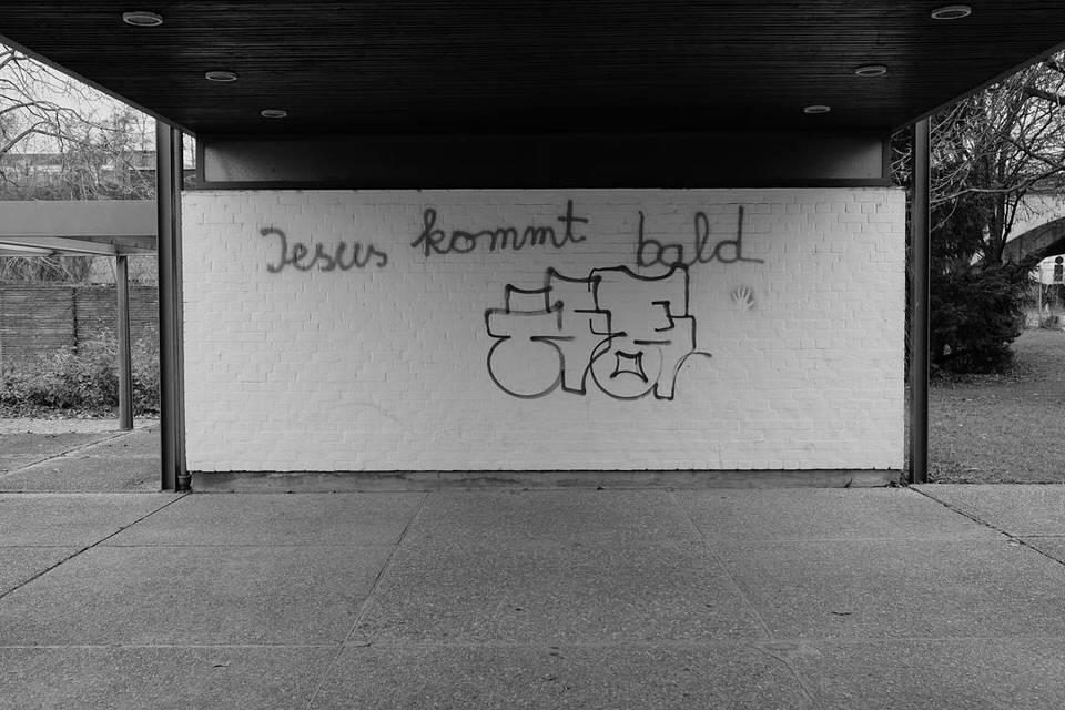 """Ansicht einer Wand auf die mit Graffiti """"Jesus kommt bald"""" gesprüht wurde."""