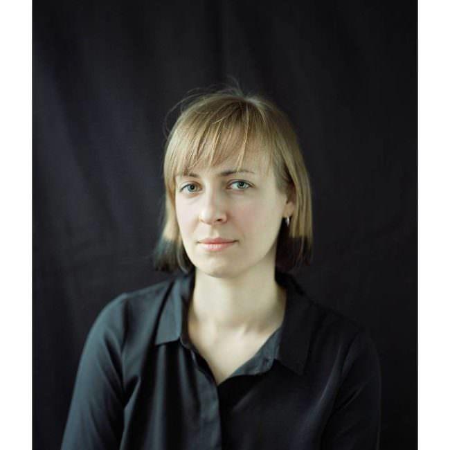 Portrait einer jungen Frau mit schulterlangen blonden Haaren die einen direkt anblickt.