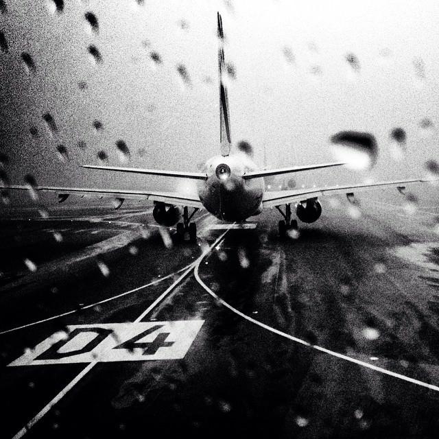 Sicht durch eine nasse Scheibe auf ein Flugzeug auf der Rollbahn.