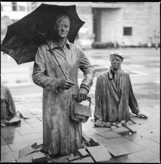 Eine Bronzefigur mit Regenschirm.