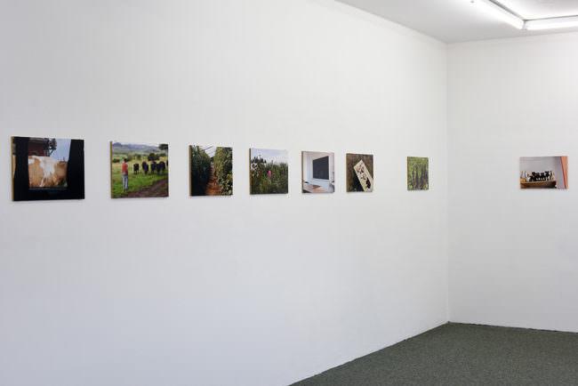 Ansicht einer Raumecke mit Fotografien an der Wand.
