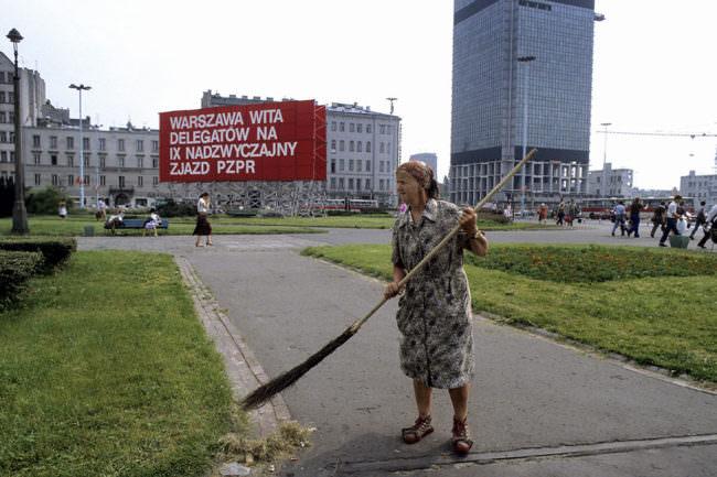 Eine ältere Dame mit Schürzenkleid fegt mit einem Reisigbesen einen Weg. Im Hintergrund sind städtische Gebäude zu sehen.