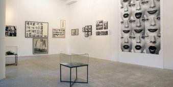 Galerieeinblick mit Schaukasten im Vordergrund und Fotografien an der Wand. Rechts deutlich erkennbare Portraits von verschiedenen Gesichtsausdrücken.