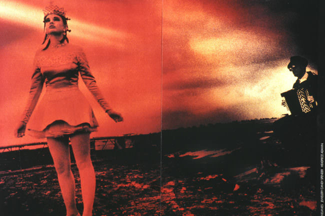 Eine Frau in weißem Kleid lehnt sich stehend nach vorn. Im Hintergrund eine Wolkenlandschaft. Alles ist rot eingefärbt.