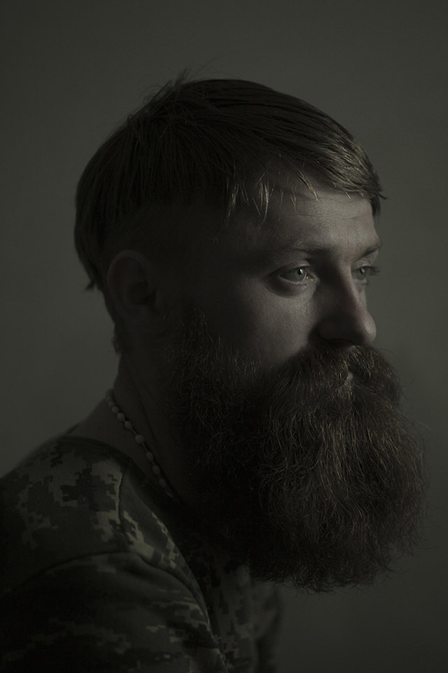 Portrait eines jungen Mannes in Flecktarn mit langem Bart. Die Lichtstimmung ist recht düster gehalten.