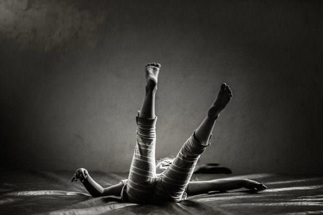 Ein Kind mit Beinen nach oben auf einem Bett
