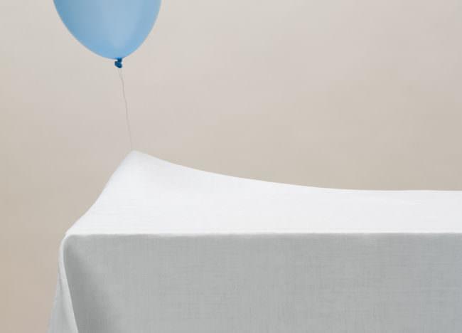 Ein blauer Luftballon an einer Schnur strebt nach oben und hängt jedoch unten an einer weißen Decke fest.