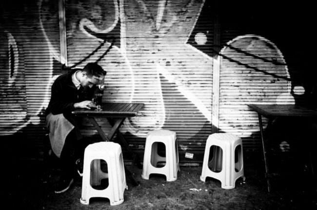 Ein Mann gebeugt an einem kleinen Tisch an einer Hauswand.