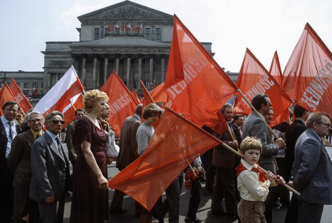 Menschen mit roten Fahnen laufen als Zug vor einem großen Gebäude vorbei. Eine Frau hält die Fahne eines Jungen mit fest.