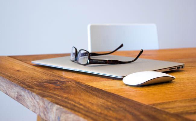 Ein Laptop und eine Brille auf einem Tisch
