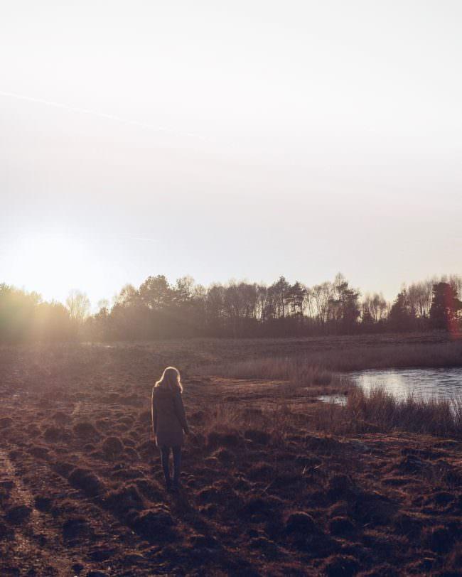 Eine Frau, die bei Sonnenuntergang an einem See entlang geht