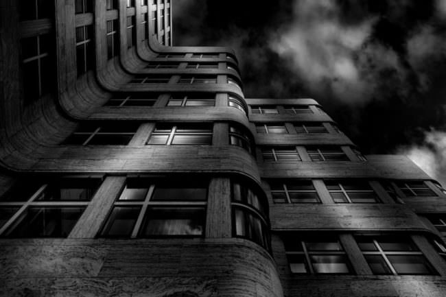 Langzeitbelichtung eines Blickes nach oben entlang eines Hochhauses.