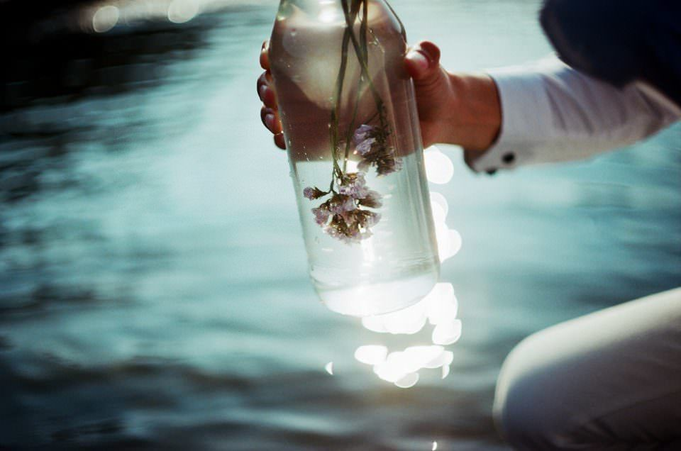 Eine Flasche in der sich eine Blume befindet wird von jemandem in der Hand gehalten.