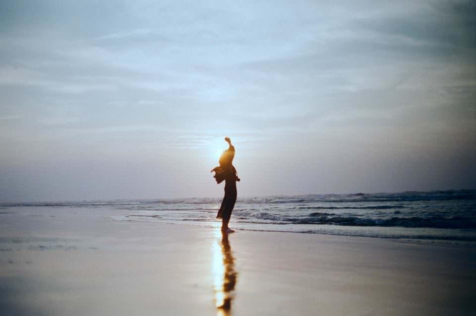 Eine Frau steht bei Sonnenuntergang am Strand.
