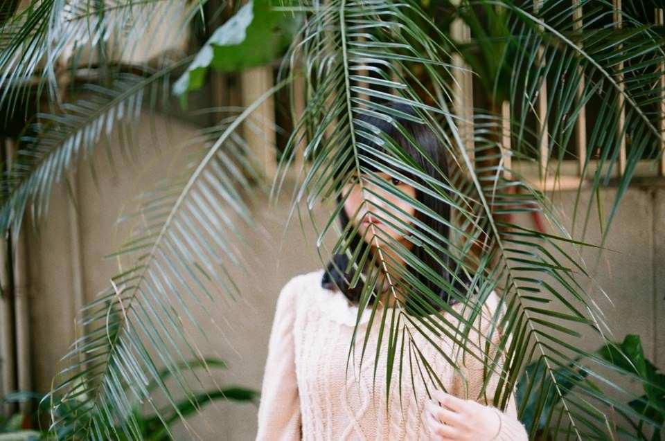 Eine Frau, die durch eine Pflanze hindurch in die Kamera blickt.