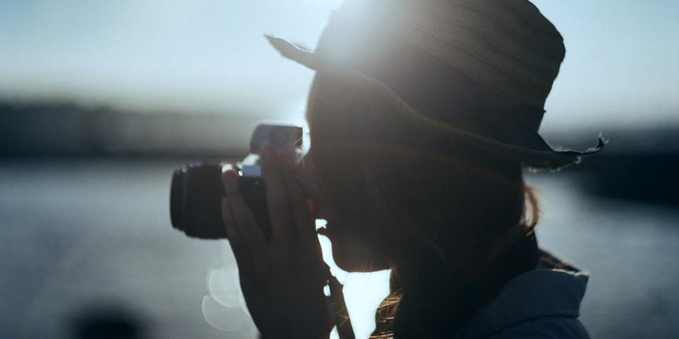 Portrait einer Frau die gerade fotografiert im Gegenlicht.