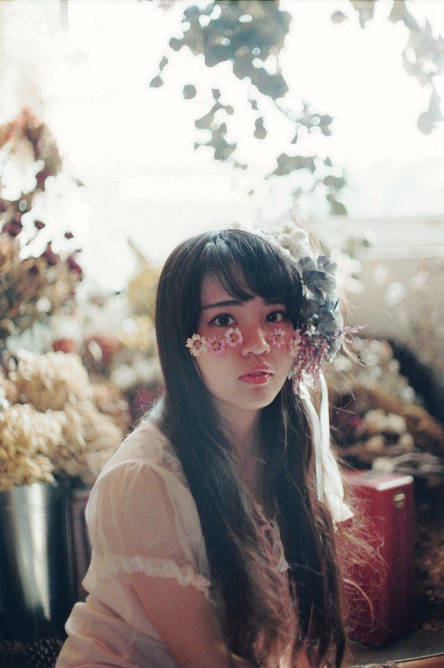 Portrait einer Frau mit Blumen auf dem Gesicht