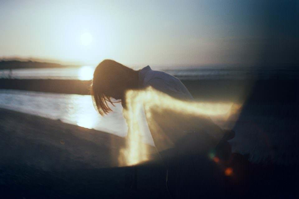 Eine Frau am Strand im Gegenlicht.