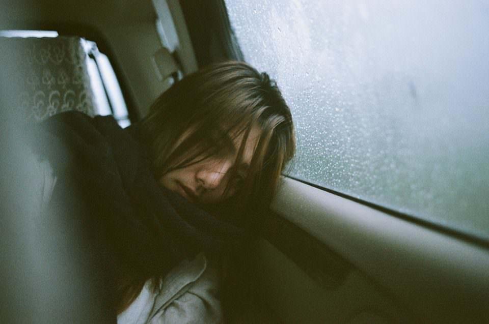Portrait einer Frau die in einem Auto sitzt und ihren Kopf an die Autotüre lehnt.