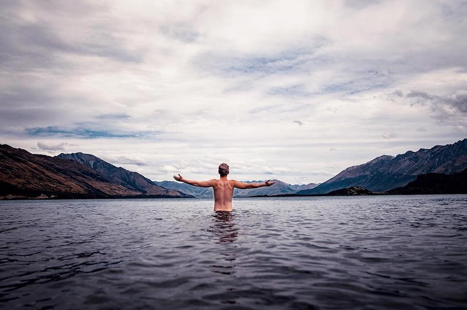 Mann mit nacktem Oberkörper in einem See vor einem Bergpanorama