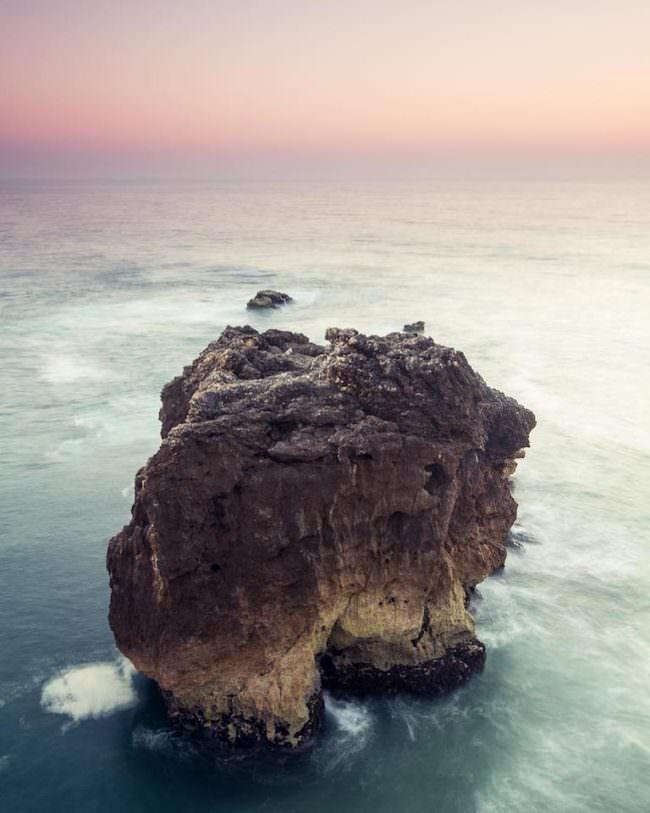 Ein Felsen im Meer bei Sonnenuntergang.